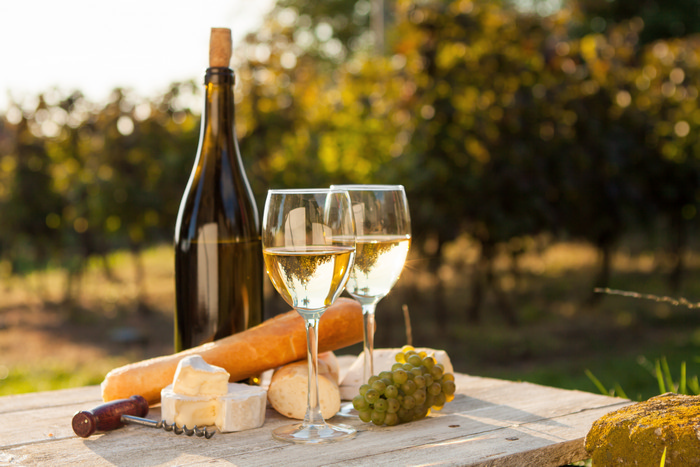 Two glasses of white wine and bottle at sunset shutterstock_156451127.jpg