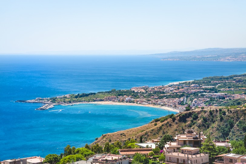 Taormina city and giardini naxos resort on the coast of Ionian sea from Castelmola village in Sicily shutterstock_604416593.jpg